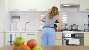 La mujer delgada de pelo largo de la opinión de la parte trasera cocina la cena en cocina agradable almacen de video