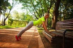 La mujer delgada deportiva que hace aptitud de los pectorales ejercita en parque Fotos de archivo libres de regalías