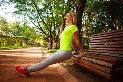 La mujer delgada deportiva que hace aptitud de los pectorales ejercita en parque Fotografía de archivo