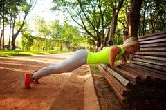 La mujer delgada deportiva que hace aptitud de los pectorales ejercita en parque Imagen de archivo libre de regalías