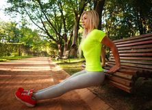 La mujer delgada deportiva que hace aptitud de los pectorales ejercita en parque Fotos de archivo