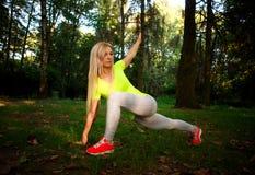La mujer delgada deportiva que hace aptitud ejercita estirar en parque Imagen de archivo