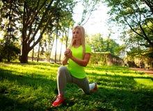 La mujer delgada deportiva que hace aptitud ejercita estirar en parque Foto de archivo