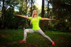 La mujer delgada deportiva que hace aptitud ejercita estirar en parque Fotos de archivo