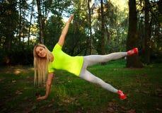 La mujer delgada deportiva que hace aptitud ejercita estirar en parque Imagenes de archivo
