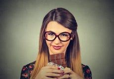 La mujer delgada en vidrios cansó de restricciones de la dieta que anhelaba el chocolate de la oscuridad de los dulces Fotos de archivo