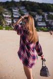 La mujer delgada hermosa en camisa, los pantalones cortos y las gafas de sol de la moda caminan en la playa Visión desde la parte Imágenes de archivo libres de regalías