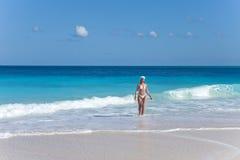 La mujer delgada joven en el bikini blanco celebra el Año Nuevo que deja ondas del mar del Caribe Fotos de archivo