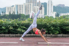 La mujer delgada joven que hace yoga abajo persigue ejercicio partido en parque de la ciudad el día de verano Atleta de sexo feme Fotos de archivo