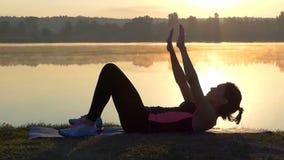 La mujer delgada miente en un banco del lago y aumenta la cabeza en la puesta del sol almacen de video