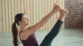 La mujer deportiva atlética hermosa que hace yoga ejercita dentro Estirar práctica en el gimnasio almacen de metraje de vídeo