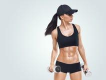 La mujer deportiva de la aptitud en el entrenamiento que bombea para arriba muscles con pesas de gimnasia Imagen de archivo libre de regalías