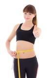 La mujer deportiva delgada hermosa con la cinta de la medida manosea con los dedos encima de aislado Imágenes de archivo libres de regalías