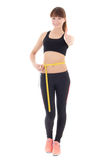 La mujer deportiva delgada hermosa joven con los pulgares de la cinta de la medida para arriba está Fotografía de archivo