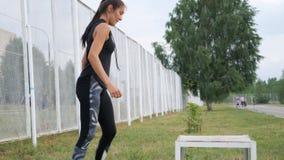 La mujer deportiva en el gimnasio que hace ejercicio apto de la cruz intensifica en la caja almacen de video