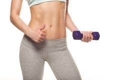 La mujer deportiva hace su entrenamiento con pesas de gimnasia Imagenes de archivo
