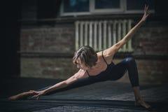 La mujer deportiva hermosa del yogini del ajuste practica asana de la yoga en el pasillo oscuro imagen de archivo libre de regalías