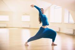 La mujer deportiva hermosa del yogini del ajuste practica el asana Virabhadrasana 1 de la yoga - la actitud 1 del guerrero en la  Imagen de archivo libre de regalías