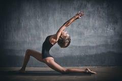 La mujer deportiva hermosa del yogini del ajuste practica el asana Virabhadrasana 1 de la yoga - la actitud 1 del guerrero en el  Fotografía de archivo libre de regalías
