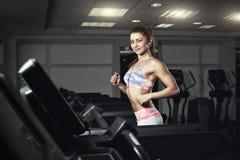 La mujer deportiva joven corre en la máquina en el gimnasio Imágenes de archivo libres de regalías