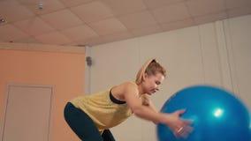 La mujer deportiva joven está haciendo posiciones en cuclillas con Fitball en las manos en gimnasio del entrenamiento almacen de video