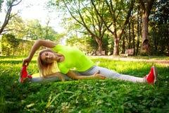 La mujer deportiva joven que hace aptitud ejercita estirar en parque Fotos de archivo