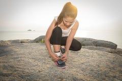 La mujer deportiva joven que se prepara para correr por mañana y el mar es backgr Imagenes de archivo