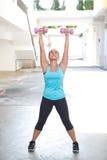 la mujer deportiva que sostenía el barbell rosado con ambos brazos estiró hacia fuera para el hombro que consolidaba, al aire lib Foto de archivo libre de regalías