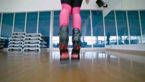 La mujer deportiva salta con los zapatos del kangoo en estudio de la danza almacen de video