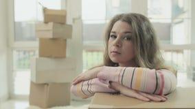 La mujer depresiva se inclina encendido desempaqueta la caja metrajes