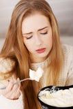La mujer deprimida joven está comiendo el cuenco grande helado al comfor Imagen de archivo libre de regalías