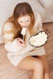 La mujer deprimida joven está comiendo el cuenco grande helado al comfor Foto de archivo