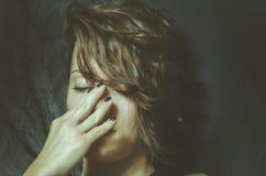 La mujer deprimida joven que siente desgraciada y sola cubre su cara con sus manos en el cuarto oscuro de su hogar Imagen de archivo