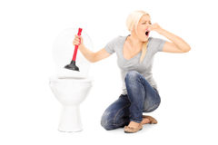La mujer desatasca un retrete stinky con el émbolo foto de archivo