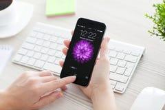 La mujer desbloquea gris del espacio del iPhone 6 sobre la tabla Foto de archivo libre de regalías