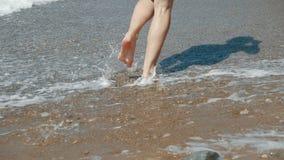 La mujer descalza deportiva activa corre a lo largo de la costa en la CÁMARA LENTA Aptitud de la mujer, entrenamiento que activa  almacen de video