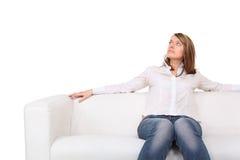 La mujer descalza hermosa joven se sienta en el sofá Fotos de archivo