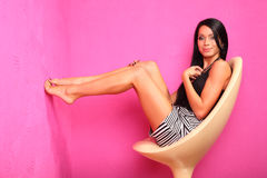 La mujer descalza sonriente se sienta en silla plástica Fotos de archivo libres de regalías