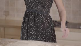La mujer desconocida en el vestido negro manchado con pasta de mezcla de la harina en manos y fuertemente lanza la pasta en metrajes
