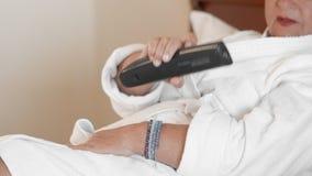 La mujer desconocida miente en una cama en un hotel en una albornoz blanca y controla la TV usando el telecontrol r almacen de metraje de vídeo