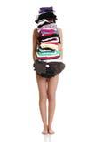 La mujer descubierta joven es permanente y que sostiene la ropa. Imagen de archivo libre de regalías