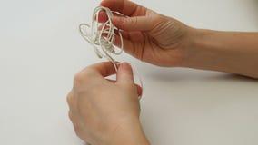 La mujer desenreda auriculares de botón o el nudo enredados del auricular metrajes
