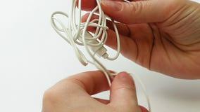 La mujer desenreda auriculares de botón o el nudo enredados del auricular almacen de video