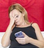 La mujer desesperada cubre su cara con una mano mientras que en la otra ella sostiene un smartphone fotos de archivo libres de regalías