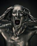 La mujer desnuda tiene gusto de la estatua en metal líquido Foto de archivo