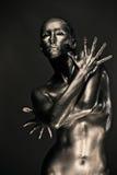 La mujer desnuda tiene gusto de la estatua en metal líquido Fotos de archivo libres de regalías
