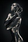 La mujer desnuda tiene gusto de la estatua en metal líquido Imagen de archivo