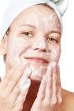 La mujer despeja una espuma de la piel de la cara fotografía de archivo