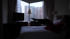 La mujer despreocupada salta en cama almacen de video