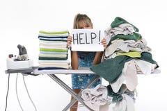 La mujer detrás de un tablero que plancha pide ayuda Foto de archivo libre de regalías